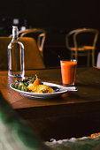 Morning breakfast, omelette with green salad on white plate with fresh orange carrot juice. Wooden table. Dark food photography concept.