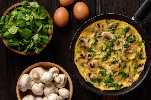 Omelette with mushrooms and cheese, on dark wooden background. stock photo