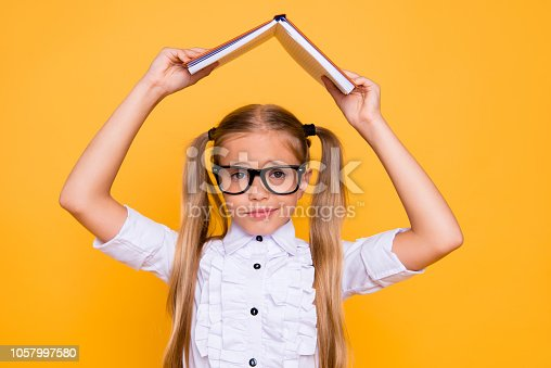 istock Omg! Back to school! Close up photo portrait of sweet lovely upset sad girt covering head with opened notebook holding above head wearing white stylish blouse isolated bright background 1057997580