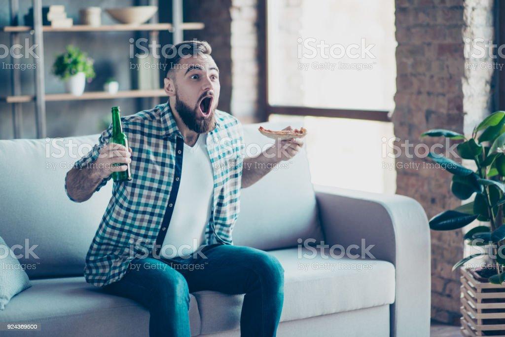 OMG! Ziel! Verrückte lustige glücklich aufgeregt erstaunt erstaunt Kerl im karierten Hemd und Jeans bekleidet, er isst Pizza und Bier trinken, auf dem Sofa sitzen und beobachtete Finale des sport-Spiel – Foto