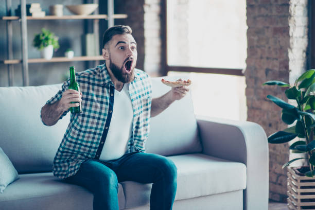 omg! goal! crazy funny happy excited astonished amazed guy clothed in checkered shirt and jeans, he is eating pizza and drinking beer, sitting on a sofa and watching final of sport game - home show stock photos and pictures