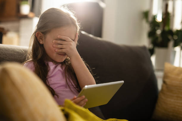 Omg, I cant watch this! Scared little girl covering her eyes while surfing the Internet on touchpad at home. shock tactics stock pictures, royalty-free photos & images