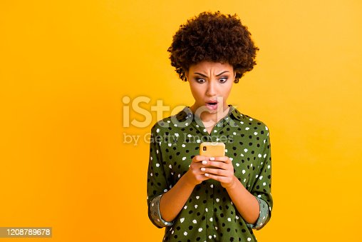 Omg its unbelievable. Astonished crazy afro american girl use smart phone read social media, information get negative reaction dislike wear stylish clothing isolated shine color background