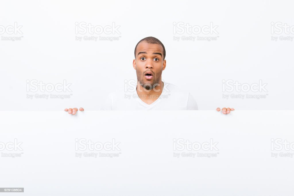 Omg! No way! Advertising concept. Confused afro man is standing behind the pure blank banner, holding it, white copyspace, in casual wear, looking at the camera, shocked with wide open eyes stock photo