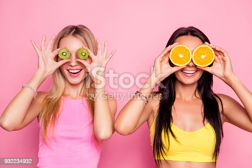 Omg! Surprised wondered astonished attractive pretty happy smiling charming joyful funky women are fooling around and covering their eyes with juice kiwi and orange, isolated on bright pink background