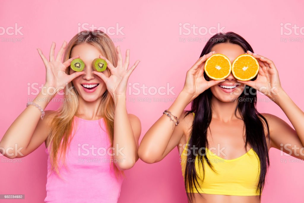 Omg! Surprised wondered astonished attractive pretty happy smiling charming joyful funky women are fooling around and covering their eyes with juice kiwi and orange, isolated on bright pink background stock photo