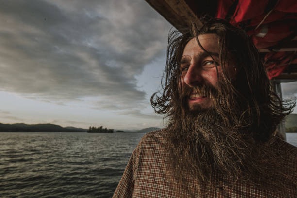 ominous dark long hair bearded sailor man on wooden boat - katiedobies stock pictures, royalty-free photos & images