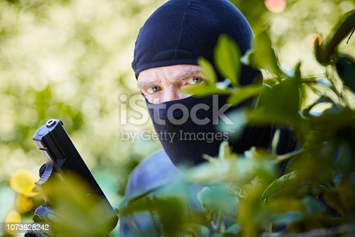 A dangerous looking man in a balaclava and holding a pistol hides among foliage staring at the camera threateningly.