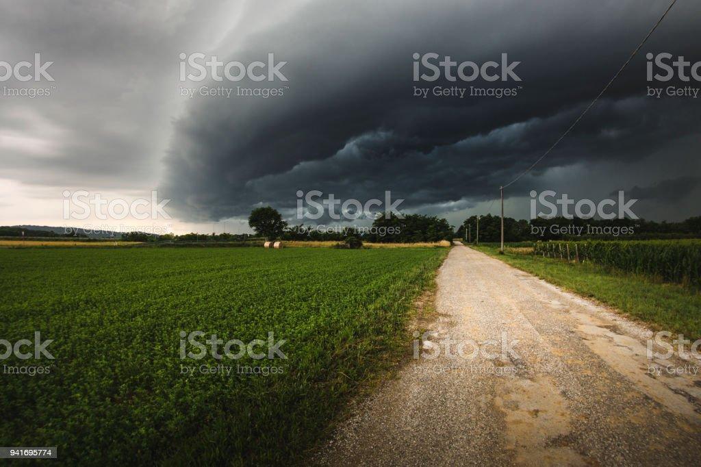 Ominous storm cloud over dirt road between corn fields stock photo