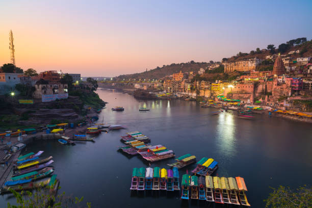Omkareshwar cityscape at dusk, India, sacred hindu temple. Holy Narmada River, boats floating. Travel destination for tourists and pilgrims. stock photo