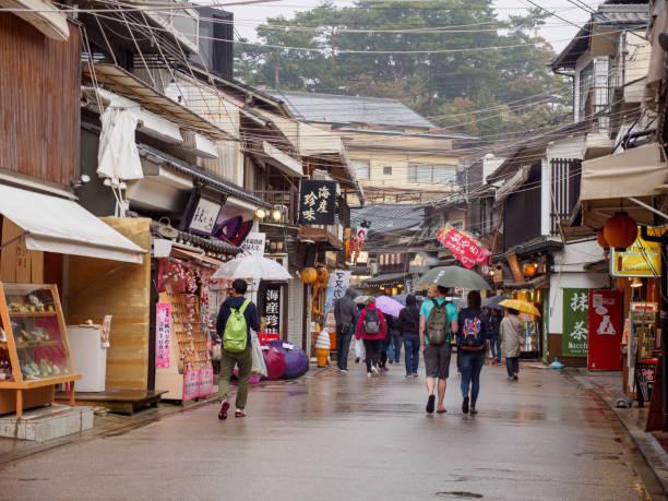 Omotesando shopping street, Hiroshima, Japan HIROSHIMA, JAPAN - APRIL 5, 2018: Wide view of tourists with umbrellas walking along the famous Omotesando Shopping Street on Miyajima Island during a rainy day. Travel and tourism. miyajima stock pictures, royalty-free photos & images