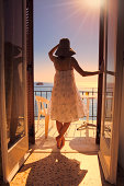 """""""A young woman on the balcony of a hotel room looking in the distance at Meditarrenean Sea with a ferry boat on it. This image was taken in Agia Marina (Aegina Island, Greece)"""""""