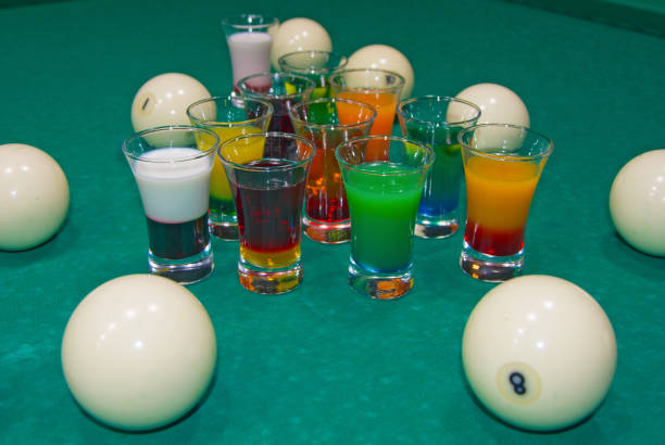 on a billiard table stand with coloured glasses of alcohol. - target australia stock pictures, royalty-free photos & images
