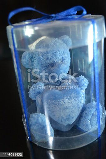 istock On a black glossy background is a blue candle in the form of a teddy bear in a package with a blue bow on top and with a reflection. 1146011420