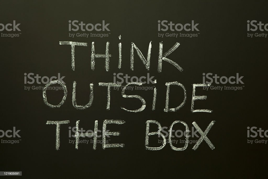 THINK OUTSIDE THE BOX on a blackboard royalty-free stock photo