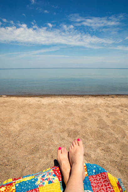 On a Blanket at the Beach in Lake Erie A woman's feet on a blanket on the beach of Lake Erie. sdominick stock pictures, royalty-free photos & images
