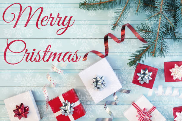 auf einem blauen hintergrund der aufschrift frohe weihnachten. weihnachten-komposition aus einem weihnachtsbaum zweig, rote und weiße geschenkboxen und dekorativen bändern. es gibt viele schneeflocken in unschärfe. urlaub-fotografie. - es schneit text stock-fotos und bilder