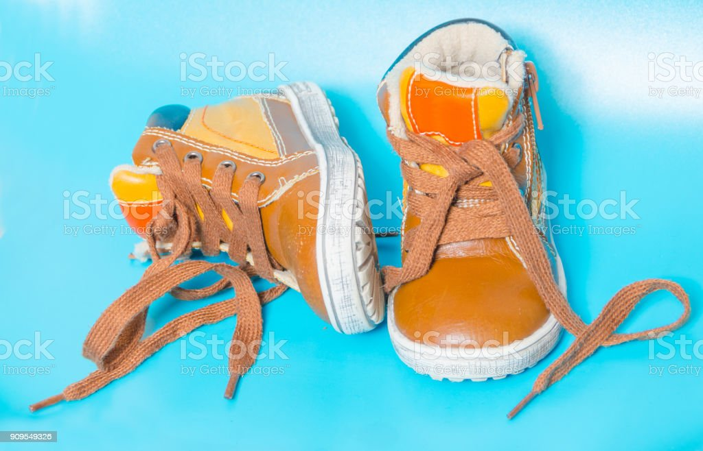 on a blue background, two children's Shoe stock photo