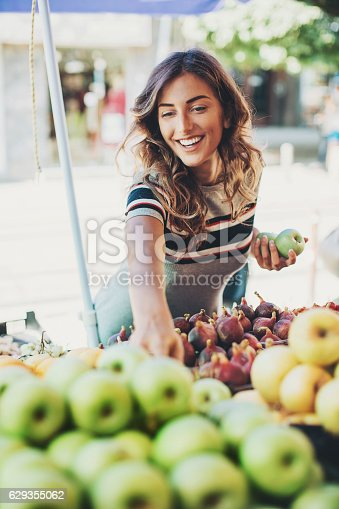 Attractive woman choosing fruits on the farmer's market.