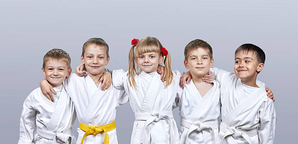 on a gray background little athletes in karategi - karate stock-fotos und bilder