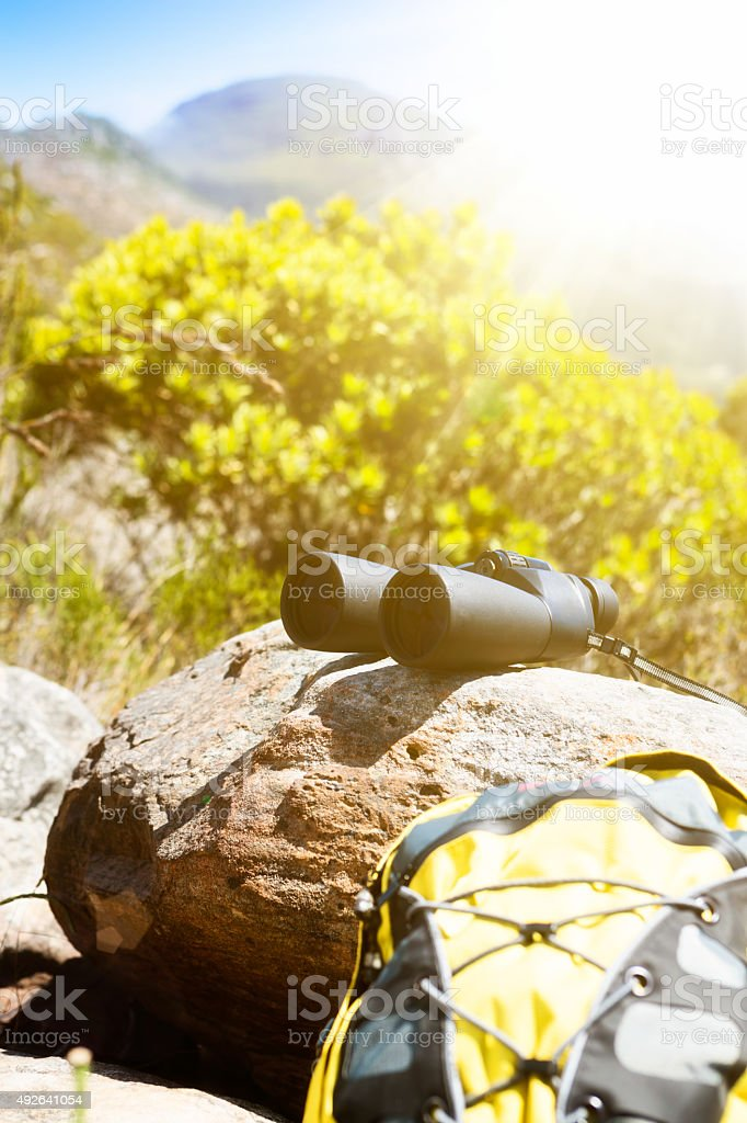 On a hike in beautiful mountainous countryside, binoculars and backpack stock photo