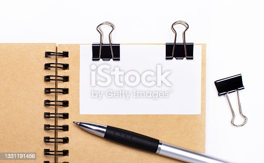 istock On a light background, a brown notebook with a pen, black clips and a white card with a place to insert text or illustrations. Template. 1331191456