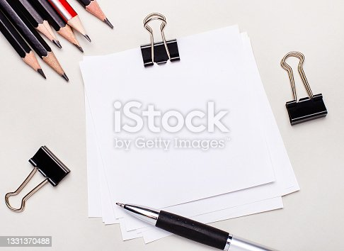 istock On a light background, black pencils, black paper clips, a pen and a blank sheet of white paper with space to insert text or illustrations. Template 1331370488