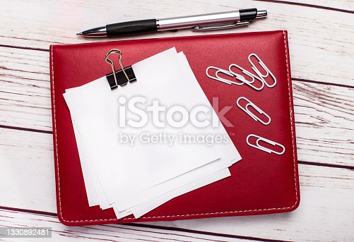 istock On a light wooden background, a pen and a burgundy notepad. On the notepad has white paper clips and white paper with space to insert text or illustrations. Template 1330892481