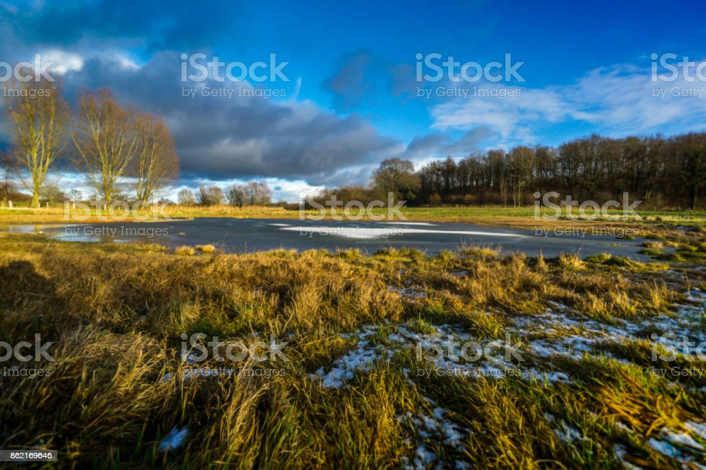 On a meadow with a half-frozen pond 3 stock photo