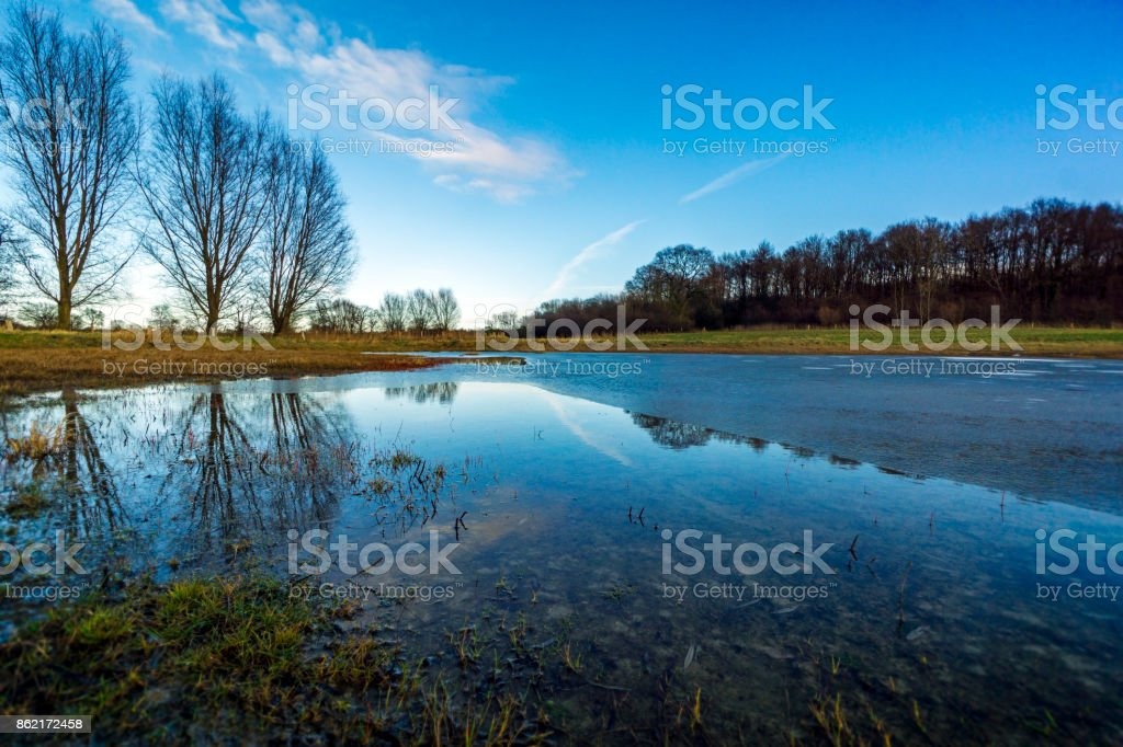 On a meadow with a half-frozen pond 5 stock photo