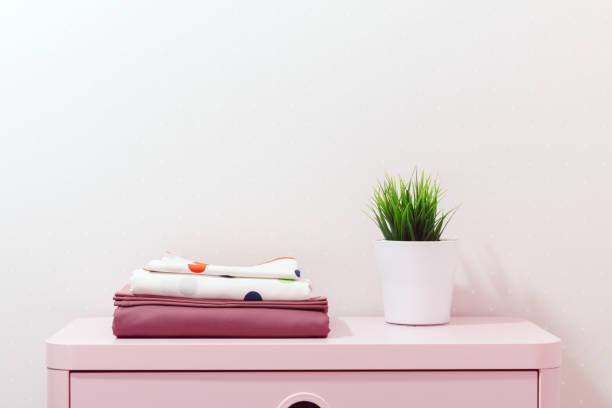auf einer rosa kommode ist ein stapel von bettwäsche und ein stammwerk - lila, grün, schlafzimmer stock-fotos und bilder