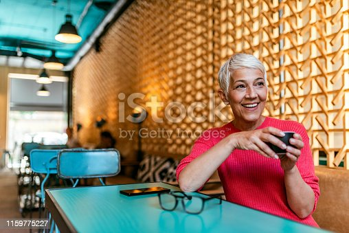 Senior businesswoman sitting at a cafe table looking away and thinking. Thoughtful mature female at the coffee shop. Photo of Elegant senior woman thinking in a restaurant. Short hair mature Woman in a coffee shop drinks coffee and thinks about the business.