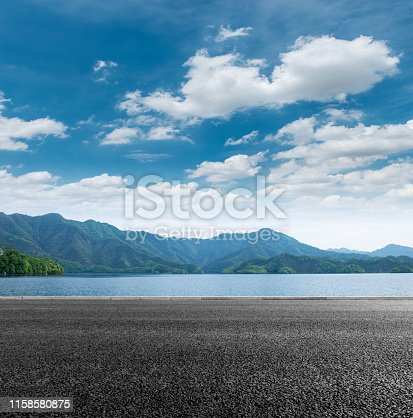 On a sunny autumn day, under the blue sky and white clouds, we can see the mountains and the wide lake,Asphalt road in front of Lake