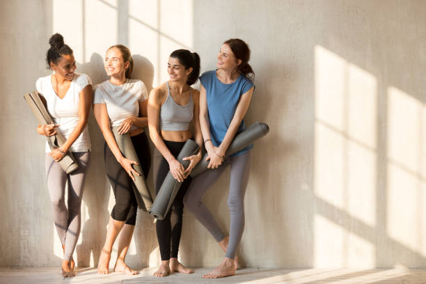 On a sunny morning girls gathered at gym for workout On a sunny morning beautiful diverse girls gathered at gym for workout. Four slim women in sportswear standing barefoot near wall holding yoga mats talking feels happy. Group training wellness concept yogi stock pictures, royalty-free photos & images
