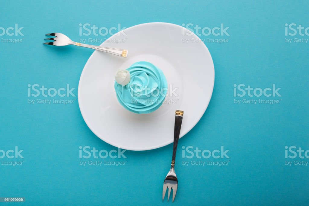 on a white plate a cake with turquoise cream and decoration, and two metal forks lie on either side, on a turquoise surface, a plate like a boat on water, a concept - Royalty-free Birthday Stock Photo