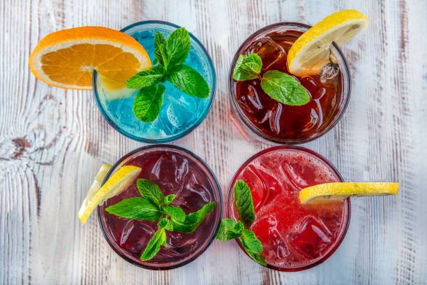 on a wooden table; blue hawaiian, ice tea, strawberry mojito and forest fruity iced drink. - напиток стоковые фото и изображения