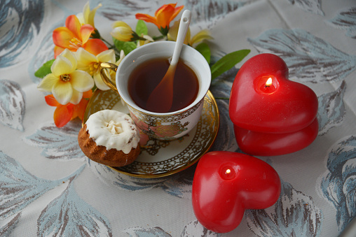 On a wooden table, tea Cup, creamer, flowers in a vase, kettle, marmalade and cakes. Breakfast on Valentine's day - tea, flowers, cake and red candles in the shape of a heart