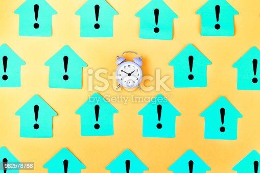 On a yellow background many blue stickers in the form of a house with exclamation marks are prikleno. In the center is a small lilac alarm clock. Concept, attention time.