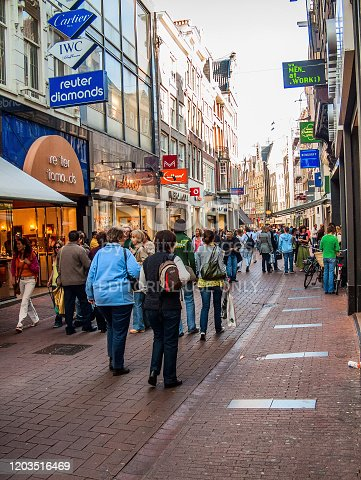 Amsterdam, Netherlands - May 5, 2007: On a narrow noisy street. The abundance of shops, cafes and tourists