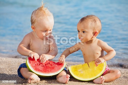 istock On beach asian and caucasian babies eat fruits fresh watermelons 509848956