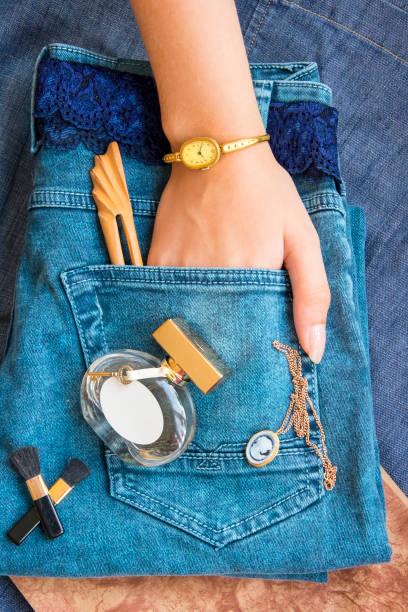 blue jeans liegen, ein parfüm-flasche, goldfiligran arbeit uhr, ein gürtel aus spitze, die hand in die tasche geschoben - goldgefüllte kette stock-fotos und bilder