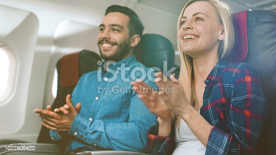 istock On Board of Commercial Airplane Beautiful Young Blonde and Handsome Hispanic Male Applauding Pilot's Successful Landing. Aerplane's Interior is Visible, Sun Shines Through Window. 1022905422