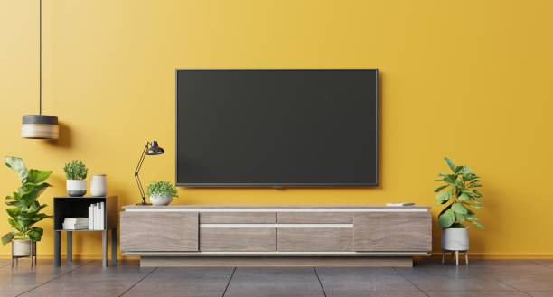 tv on cabinet in modern living room on yellow wall background. - televisor imagens e fotografias de stock