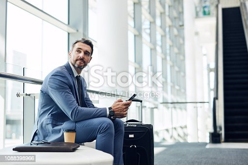 Shot of a mature businessman using a mobile phone in an airport