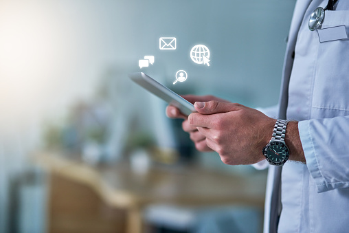 Cropped shot of a doctor receiving notifications on a digital tablet