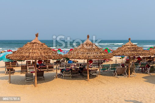 DaNang, Vietnam--March 23, 2016. Sun bathers relax on lounge chairs under thatched roof umbrellas on China Beach.