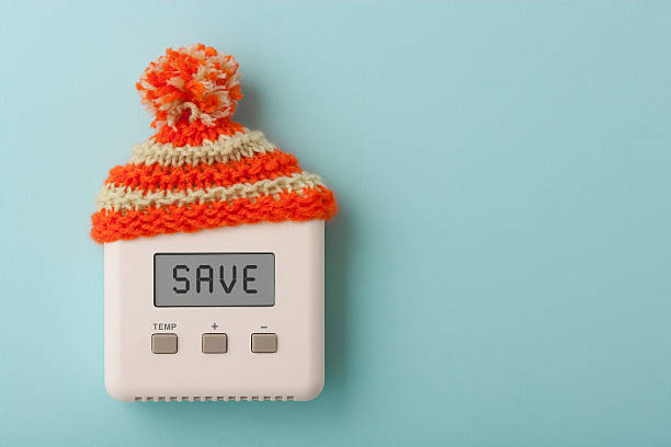 save on digital room thermostat with wooly hat - warmte stockfoto's en -beelden