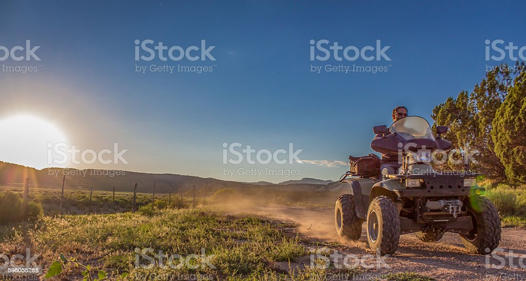 ATV on dirt road at sunset stock photo