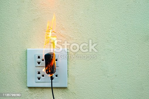 istock On fire electric wire plug Receptacle wall partition,Electric short circuit failure resulting in electricity wire burnt 1135799260