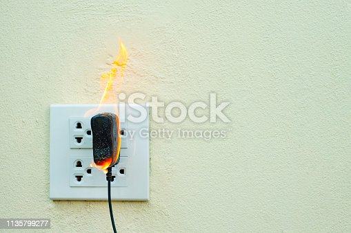 istock On fire electric wire plug Receptacle wall partition,Electric short circuit failure resulting in electricity wire burnt 1135799277